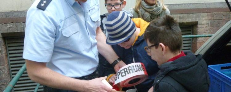 Ein Polizist erklaert uns wozu die Polizei Absperrband braucht
